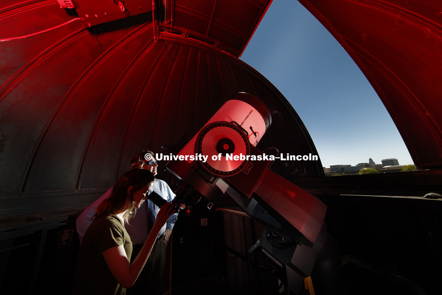 In the observatory atop the stadium parking garage, Hannah Paxton, senior in advertising and marketing, and Teaching Assistant for Professor Sibbernsen, eyes the skies under the supervision of Michael Sibbernsen, Lecturer of Astronomy- University of
