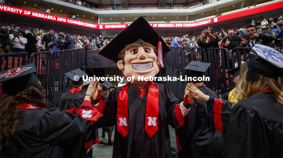 Herbie Husker, decked out in his graduation cap and gown, high fives graduates as they leave the arena. December Undergraduate commencement at Pinnacle Bank Arena. December 21, 2019. Photo by Craig Chandler / University Communication.