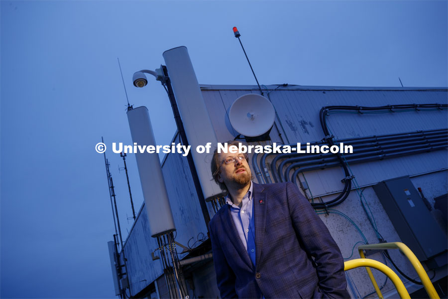 Gus Hurwitz, Nebraska Law professor researching rural broadband issues in Nebraska. He is standing amongst the telecommunications equipment that covers the roof of Oldfather Hall. January 31, 2020. Photo by Craig Chandler / University Communication.
