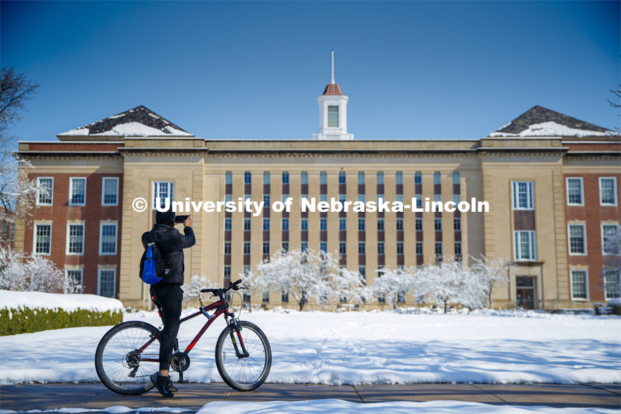 A young man riding by stops to take a picture of Love Library. An April snowstorm leaves campus unseasonably beautiful. April 17, 2020. Photo by Craig Chandler / University Communication.
