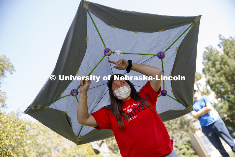 Makena Ninete describes the structure of her hat and shelter. Sharon Kuska's ARCH 231 - Structural Fundamentals class had to build a structure that promotes social distancing using structural fundamentals and sustainable materials. September 22, 2020. Photo by Craig Chandler / University Communication.