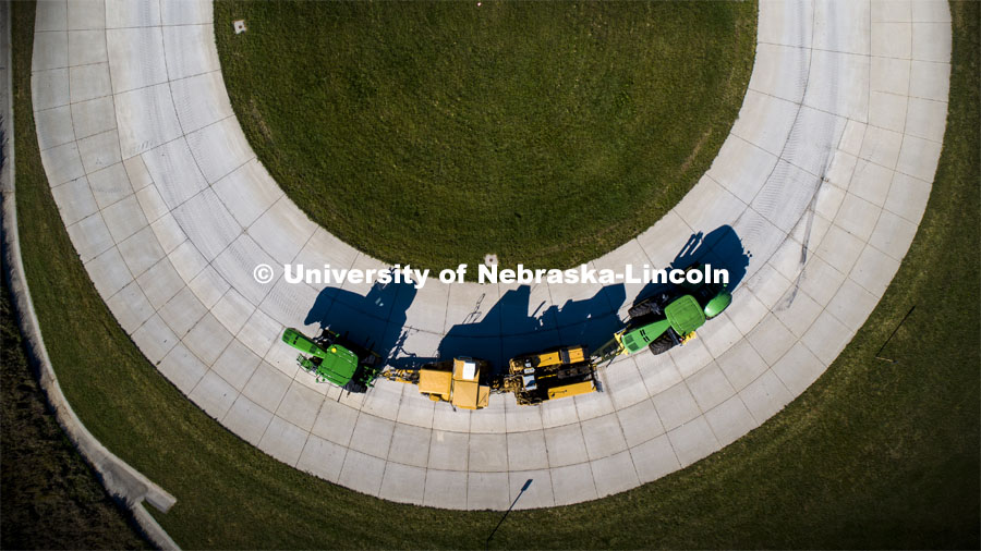 A tractor pulls the test car (yellow) and an additional tractor for weight as it rounds the test track on east campus. The University of Nebraska Tractor Test Laboratory (NTTL) is the officially designated tractor testing station for the United States. It has operated for more than 100 years. East Campus. September 28, 2020. Photo by Craig Chandler / University Communication.