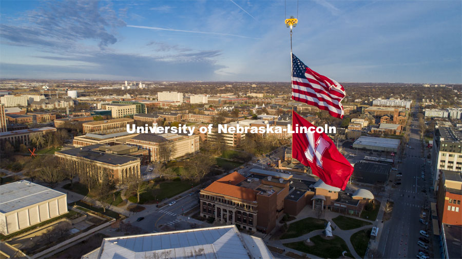 With the campus as the background, The United States and Husker flags fly on a sunny Friday afternoon from the Hausmann Construction crane being used to build the Lied Place Residences. The flags are each measure 25 x 15 feet. November 20, 2020. Photo by Craig Chandler / University Communication.