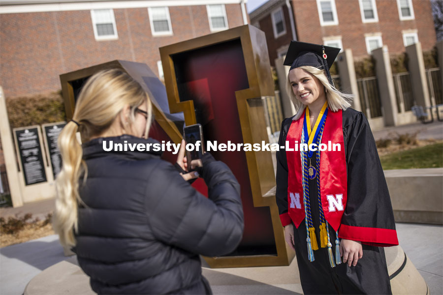 Paige Heitkamp, a senior in Criminal Justice from Sioux Falls is photographed by Jessica Kistaitis in front of The Value of N sculpture at the alumni center. December 8, 2020. Photo by Craig Chandler / University Communication.