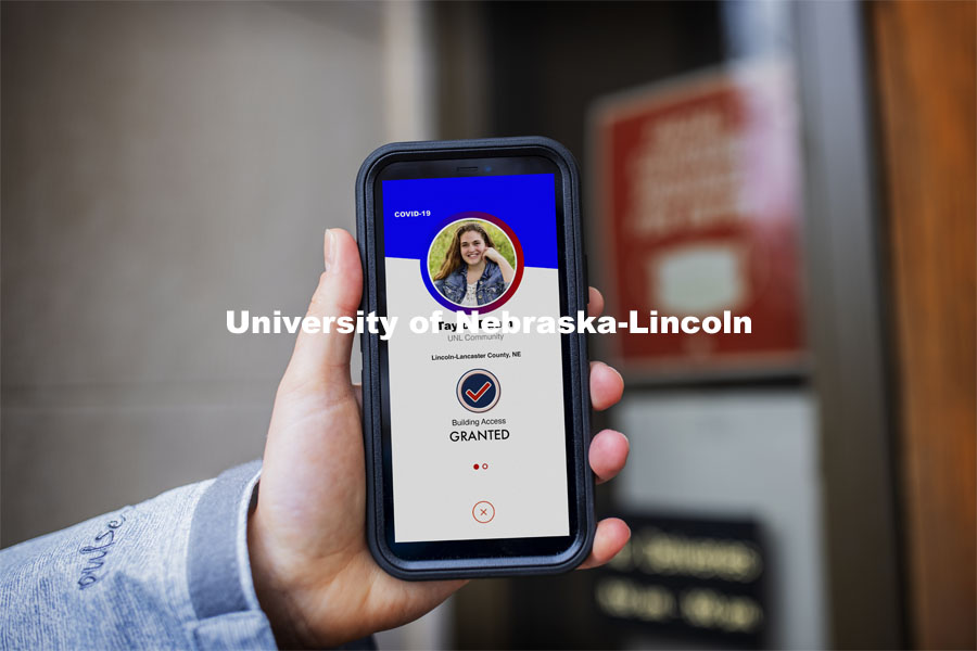 Taylor Daum shows the Safer Community app to be used as part of COVID testing on campus this spring. Phone screen is simulated and may change slightly in the final rollout. January 8, 2021. Photo by Craig Chandler / University Communication.