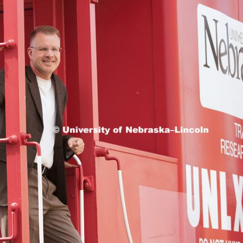 Dr. Shane Farritor poses on a caboose custom painted and donated to the University of Nebraska–Lincoln. The Husker red caboose was used to house the measuring equipment and generators used on the first-generation test car. The current test car is a self