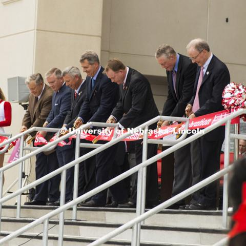 From left John Sampson, President of Sampson Construction,  University of Nebraska Regent Tim Clare, Nebraska Gov. Dave Heineman, NU President James B. Milliken, Director of Athletics Shawn Eichorst,  Athletic Director Emeritus Tom Osborne, and UNL Chancellor Harvey Perlman cut the ribbon to celebrate the expansion and new research space. University officials, state and city leaders, representatives of the Big Ten Conference and supporters staged a celebration for the historic expansion of Memorial Stadium's east side.  August 22, 2013. Photo by Greg Nathan/ University Communications