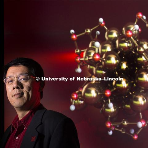 Xiao Zeng, Professor of Chemistry, Physics & Astronomy stands before a rendering of the gold nano particles. April 13, 2015. Photo by Craig Chandler / University Communications
