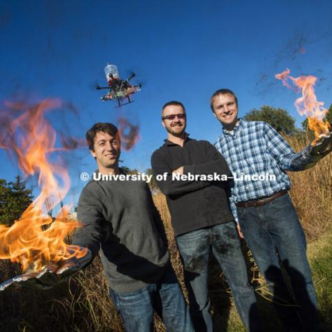 Sebastian Elbaum, left, Dirac Twidwell and Carrick Detweiler are on fire with their new patent for setting range fires with small drones. Elbaum and Detweiler hold flaming table tennis ball similar to the ones carried by the drone flying above them. The drone injects a liquid into the plastic spheres to start a delayed fiery process so the balls can fall to the ground before igniting. Elbaum and Detweiler are professors of computer science and engineering. Twidwell is an assistant professor and gangland ecologist in the school of natural resources. October 29, 2015. Photo by Craig Chandler / University Communications