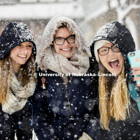 Kayla Felix, left, and Alli Hauger smile as Emily Hames takes a selfie of them while they walked to class during the hardest snow. A snow storm of large wet flakes falls on UNL Monday, January 25 2016. Photo by Craig Chandler / University Communications