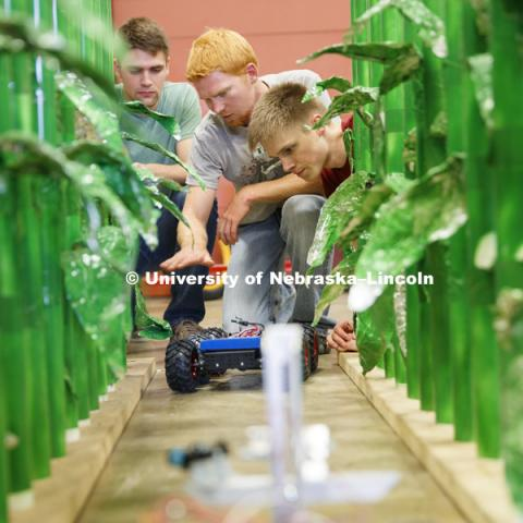 Ethan Nutter, graduate student in mechanized systems management discusses a robotic vehicle which is being developed to count seedlings in a corn row to measure germination. Tyler Troyer, graduate student in BSE, is at left and Lukas Renker, senior in