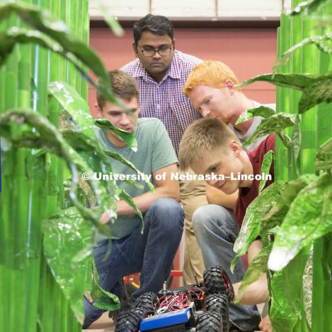 Lukas Renker, senior in Mechanical Engineering, prepares a robotic vehicle which is being developed to count seedlings in a corn row to measure germination. Professor Santosh Pitla, Tyler Troyer, graduate student in BSE, and Ethan Nutter, graduate student