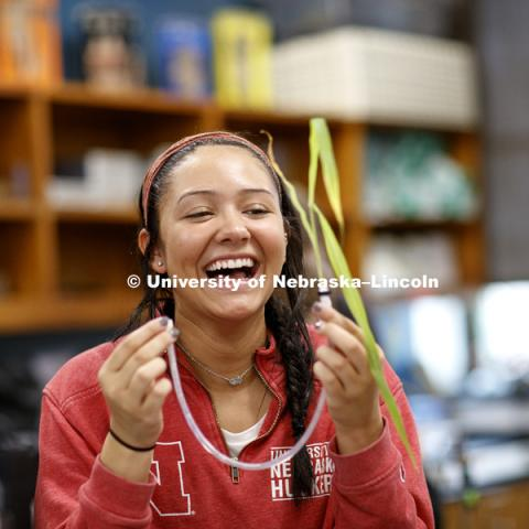 "Angeanette Russert laughs after successfully attaching a plant to a water-filled tube as part of her group experiment to measure photosynthesis. Students in LIFE 121L - Fundamentals of Biology 2 Laboratory, taught by Altangerel ""Auggie"" Tsogtsaikhan,"