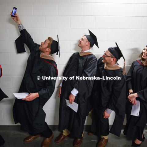 Tommie Bardsley takes a selfie before commencement with his fellow Masters Degree graduates in Business. Students earning graduate and professional degrees received their diplomas Friday afternoon in Lincoln's Pinnacle Bank Arena. Undergraduate
