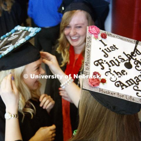 Abbey Foglesong helps Kourtney Nobel with her mortarboard before commencement. Students received their undergraduate diplomas Saturday morning in Lincoln's Pinnacle Bank Arena. 2452 degrees were awarded Saturday morning. May 6, 2017. Photo by Craig