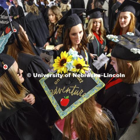 Future teachers and their decorated mortarboards congregate in the hallways of Pinnacle Bank Arena as the students arrive for commencement. Students received their undergraduate diplomas Saturday morning in Lincoln's Pinnacle Bank Arena. 2452 degrees were