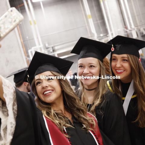 Taylor St. Peter, Avery Sass and Briley Moates take a selfie before commencement after lining up in the hallways off the arena floor. Students received their undergraduate diplomas Saturday morning in Lincoln's Pinnacle Bank Arena. 2452 degrees were