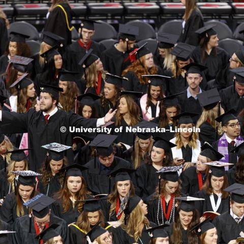 A graduate tries to make it easier for his family and friends to see where he is sitting as the graduates file into the arena. Students received their undergraduate diplomas Saturday morning in Lincoln's Pinnacle Bank Arena. 2452 degrees were awarded