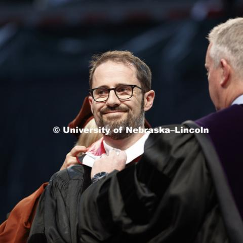 "Evan Williams, Nebraska native and founder of Twitter, receives an honorary degree before he delivered the Commencement Address ""Farm Kid Swipes Fire"". Williams is receiving help with his hood from Donde Plowman, Executive Vice Chancellor and Chief"