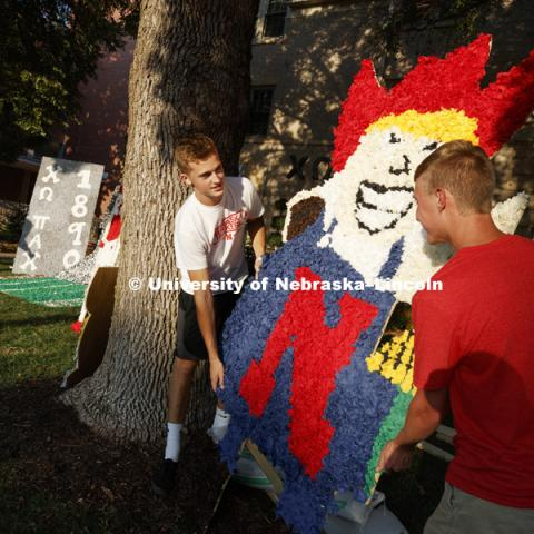 Adam Long and Chandler Brock position a pomped Herbie Husker on the display on the Chi Omega lawn. Homecoming lawn displays. September 21, 2017. Photo by Craig Chandler / University Communication.