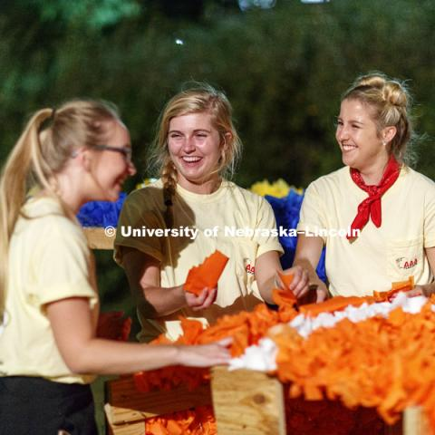 Ellie Robertson, Morgan Dickey and Taylar Zubrod, all of Delta Delta Delta, laugh while working on a Homecoming lawn display. September 21, 2017.  Photo by Craig Chandler / University Communication.
