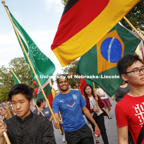 International students carry flags from their homelands in the Homecoming Parade. Homecoming parade, pep rally and court jester competition. September 22, 2017. Photo by Craig Chandler / University Communication.