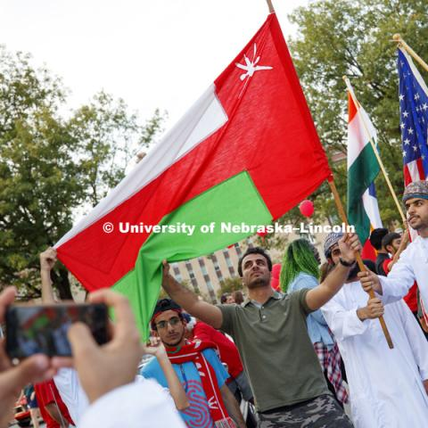 Students from Oman pose with their flag for a photo after the parade. Homecoming parade, pep rally and court jester competition. September 22, 2017. Photo by Craig Chandler / University Communication.