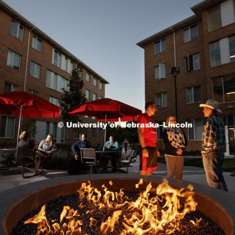Students warm themselves by the fire pit outside of Massengale Residence Hall on East Campus, October 11, 2017. Photo by Craig Chandler / University Communication.