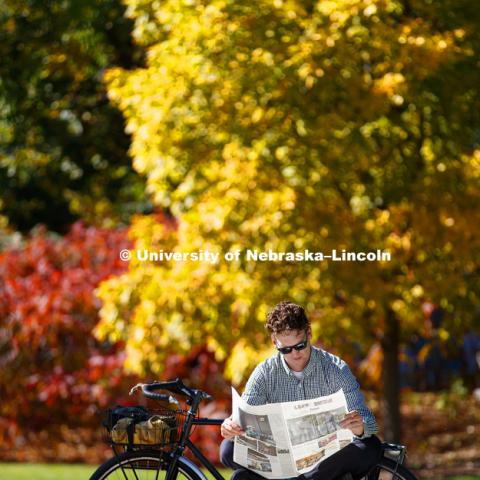 Andrew Kosmicki read the paper while enjoying the sunshine outside Adele Coryell Hall Learning Center in Love Library North. October 18, 2017. Photo by Craig Chandler / University Communication.