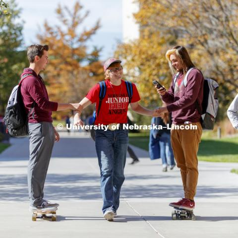 Ryan Melanson, left, and Edward Sierra-Lee are powered by Garrett Brentlinger as the three walk and roll in between classes Wednesday. City Campus fall day. October 25, 2017. Photo by Craig Chandler / University Communication.