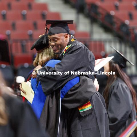 Joshua Kalu hugs Interim Dean Beth Doll after receiving his CEHS diploma. Undergraduate Commencement at Pinnacle Bank Arena. December 16, 2017. Photo by Craig Chandler / University Communication.