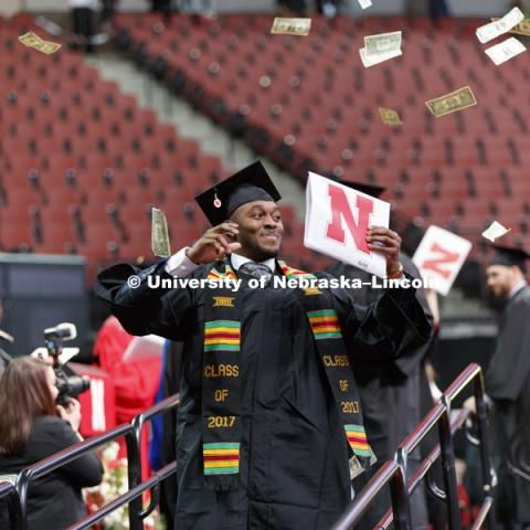 Joshua Kalu shows off his CEHS diploma after tossing a hand full of dollar bills into the air as he walked off the stage. Undergraduate Commencement at Pinnacle Bank Arena.  December 16, 2017. Photo by Craig Chandler / University Communication.