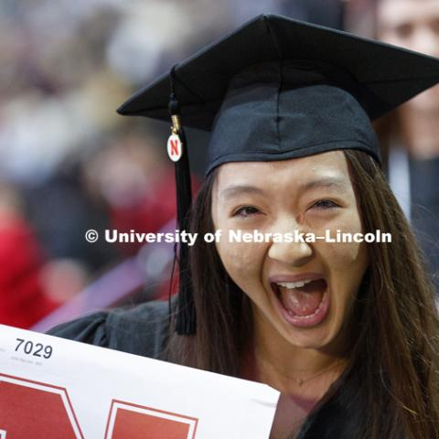 Julia Nguyen cheers after receiving her journalism degree. Undergraduate Commencement at Pinnacle Bank Arena. December 16, 2017. Photo by Craig Chandler / University Communication.