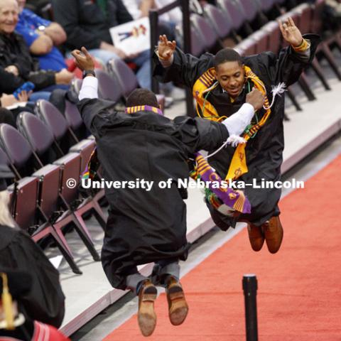 Kristoffer Bridges and an Omega Psi Phi fraternity brother celebrate on the floor after receiving their diplomas Saturday. Undergraduate Commencement at Pinnacle Bank Arena. December 16, 2017. Photo by Craig Chandler / University Communication.
