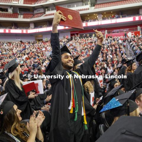Nadir Al Kharusi shows off his diploma to family and friends Saturday.  Al Kharusi, from Oman, stood after Chancellor Green asked first Nebraska residents, then non-Nebraska residents and finally international graduates to stand and be recognized.
