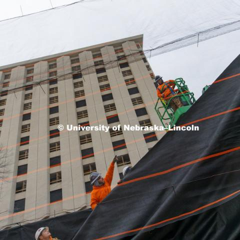 Worker with Ark Wrecking hang fabric over a mesh wall erected along 17th street in Lincoln. The wall will keep any dust and debris from the Cather Pound implosion from reaching the Knoll Residence Hall and Willa Cather Dining Center across the street from