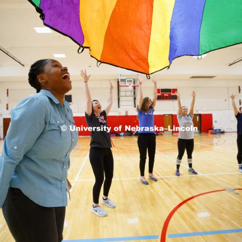Tanika Cooper, left, reacts as the students watch the parachute float back to the floor. Masters students in TEAC 893 Seminar Workshop in Health & Physical Education apply learning principals to physical education games in Mabel Lee hall gymnasium.