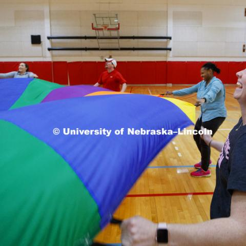 Katie Samson watches as a ball is bounced around by the student teachers using a parachute. Masters students in TEAC 893 Seminar Workshop in Health & Physical Education apply learning principals to physical education games in Mabel Lee hall gymnasium.