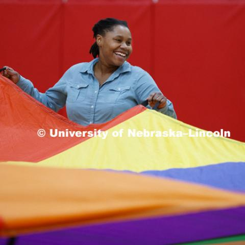 Tanika Cooper, left, reacts as the student teachers use a parachute in class. Masters students in TEAC 893 Seminar Workshop in Health & Physical Education apply learning principals to physical education games in Mabel Lee hall gymnasium.  January 12, 2018