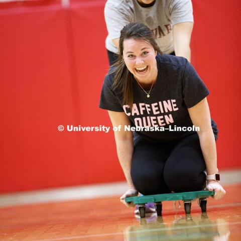Emily Hetmanek is pushed by Miranda Fendrich as they work with scooters. Masters students in TEAC 893 Seminar Workshop in Health & Physical Education apply learning principals to physical education games in Mabel Lee hall gymnasium.  January 12, 2018.
