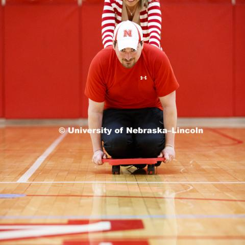 Chris Berggren is pushed by Ashley Durst as they work with scooters. Masters students in TEAC 893 Seminar Workshop in Health & Physical Education apply learning principals to physical education games in Mabel Lee hall gymnasium.  January 12, 2018. Photo