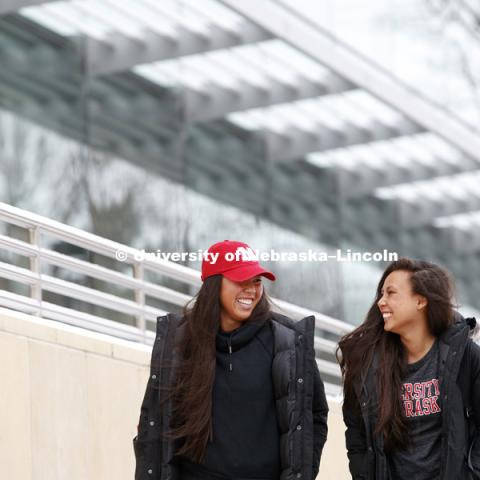 Lily Nguyen, senior in management, left, and Tammy Nguyen, junior in management, walk out of the College of Business building after classes Tuesday. Snowy day. January 23, 2018. Photo by Craig Chandler / University Communication.