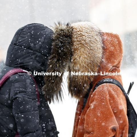 Fangyi Zhai and Miao Hong use the hoods of their coats to make it easier to talk in between classes Monday. Snow on campus. February 5, 2018. Photo by Craig Chandler / University Communication.