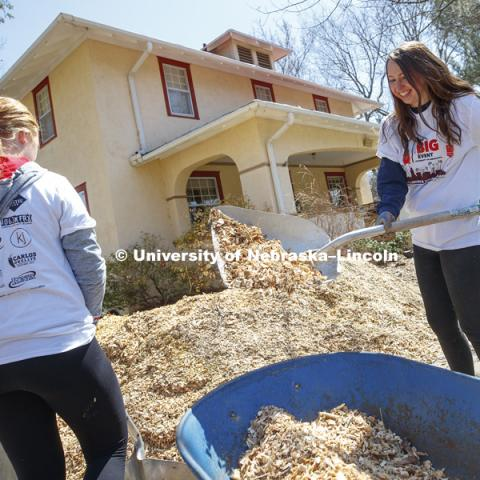 Haley Stellingwerf, Lincoln, and her Newman Center team tackle a large pile of mulch along 37th Street. Big Event. April 7,  2018. Photo by Craig Chandler / University Communication.