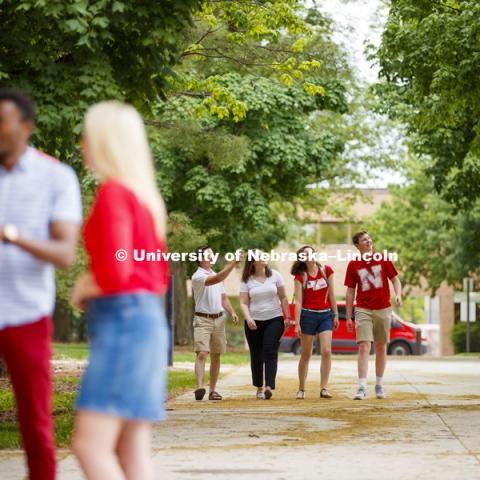 Students laughing and talking together as they cross East Campus. CASNR photo shoot on East Campus. May 29, 2018. Photo by Craig Chandler / University Communication.
