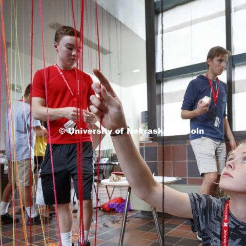 High School summer camp students in Architecture make string designs in the Link of Architecture Hall. June 21, 2018. Photo by Craig Chandler / University Communication.