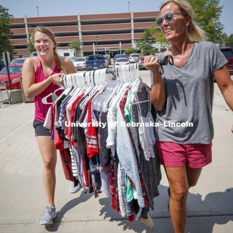 Sidney Therkelsen and her mom, Jodi, carry a rod full of clothes into Smith Hall Sunday afternoon. Housing move in for sorority rush week. August 12, 2018. Photo by Craig Chandler / University Communication.