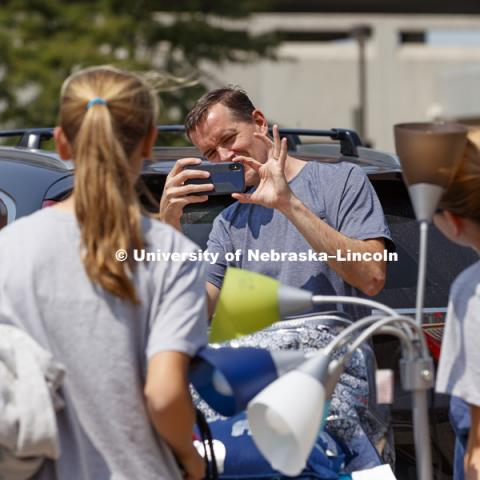 Mike Zimmerman from Liberty, Missouri, takes a photo of daughters including new freshman Emily Zimmerman who was moving into Smith Hall at the start of sorority rush week. August 12, 2018. Photo by Craig Chandler / University Communication.