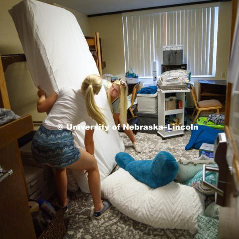 Abby Johnson works on setting up her new residence hall room as she and her sister lift the mattress onto the bed loft. Housing move in for sorority rush week. August 12, 2018. Photo by Craig Chandler / University Communication.