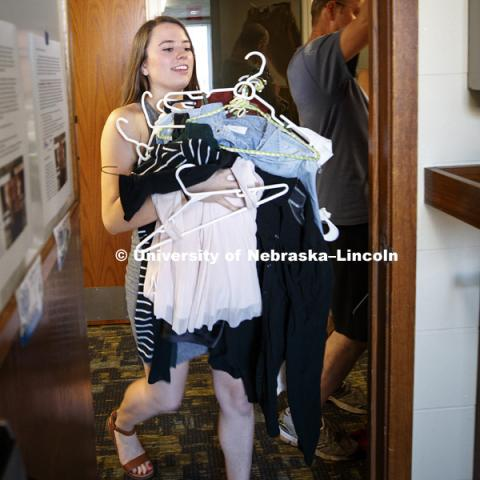 Hannah Cass carries an armload of clothes into her room Sunday afternoon. Housing move in for sorority rush week. August 12, 2018. Photo by Craig Chandler / University Communication.